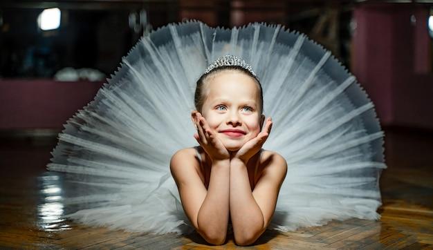 Kleines ballerina-mädchen in einem weißen tutu. entzückendes kind, das auf boden in einem studio liegt.