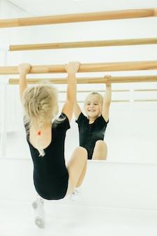 Kleines ballerinamädchen im schwarzen. entzückendes kind, das klassisches ballett in einem weißen studio tanzt. kinder tanzen. kinder durchführen. junge begabte tänzerin in einer klasse. vorschulkind, das kunstunterricht nimmt.