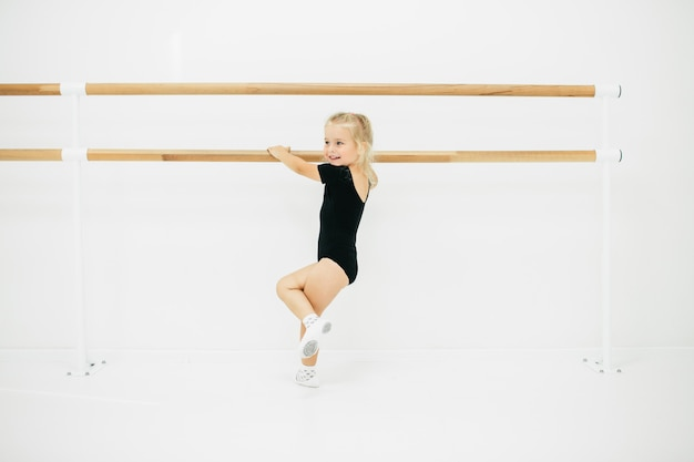 Kleines ballerinamädchen im schwarzen. entzückendes kind, das klassisches ballett tanzt. kinder tanzen. kinder durchführen. junge begabte tänzerin in einer klasse. vorschulkind, das kunstunterricht nimmt.