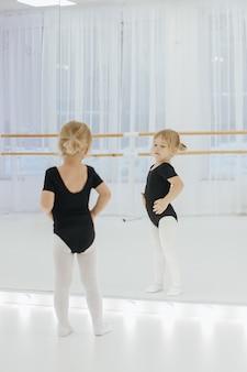 Kleines ballerinamädchen im schwarzen. entzückendes kind, das klassisches ballett tanzt. kinder tanzen. kinder durchführen. junge begabte tänzerin in einer klasse. vorschulkind, das tanzstunden nimmt.