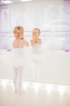 Kleines ballerinamädchen im weißen ballettröckchen, das nahe bei dem spiegel mit ihrer reflexion in ihm am tanzstudio steht. kinder- und ballettkonzept.