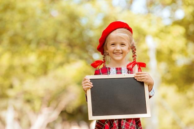 Kleines blondes erstklässlermädchen im roten kleid und im barett, die ein leeres reißbrett halten
