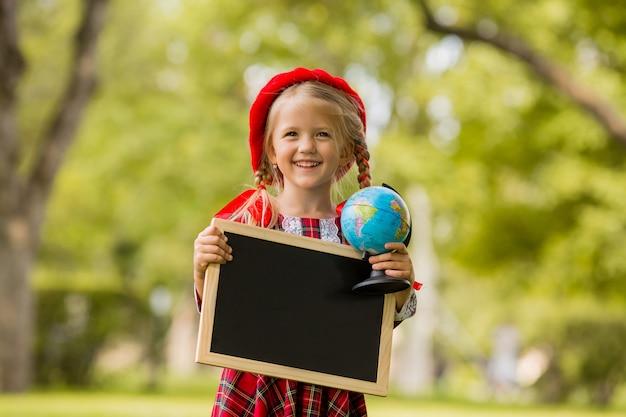 Kleines blondes erstklässlermädchen im roten kleid und im barett, die ein leeres reißbrett und eine kugel halten