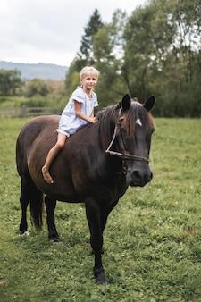 Kleines blondes kindermädchen im kleid, das ein pferd reitet.