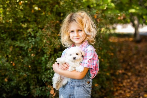 Kleines blondes kleinkindmädchen mit zwei zöpfen, die mit netten weißen welpen spielen