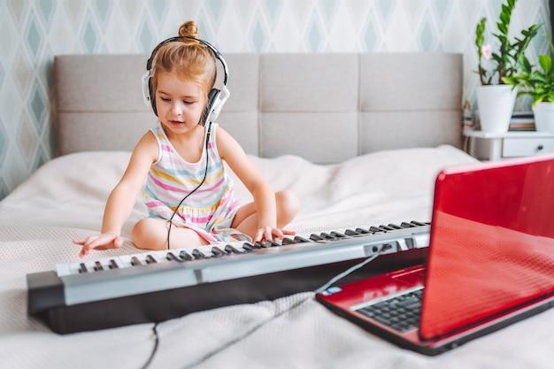 Kleines blondes kleinkindmädchen spielen klassisches digitales klavier zu hause während der online-lektion mit laptop.