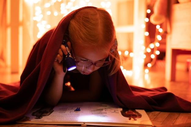 Kleines blondes mädchen 7 jahre alt mit gläsern das buch unter der decke mit weniger taschenlampe in der dunklen nachtzeit lesend