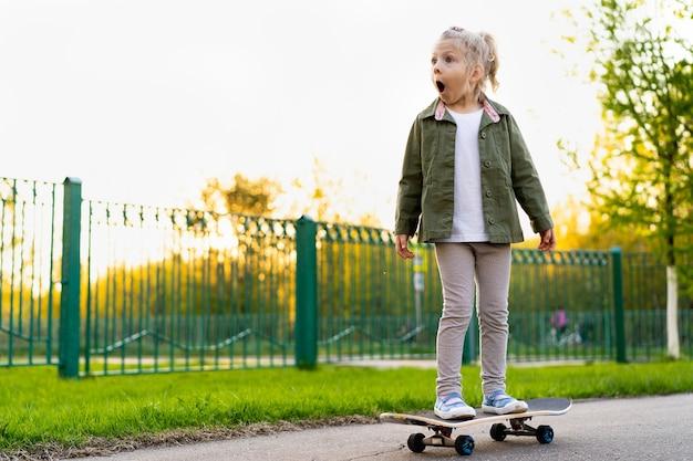 Kleines blondes mädchen auf einem skateboard in der stadt.
