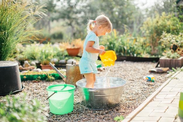 Kleines blondes mädchen, das am garten mit wasser in einem zinnbecken spielt. gartenarbeit für kinder. sommerspaß im freien. kindheit auf dem land