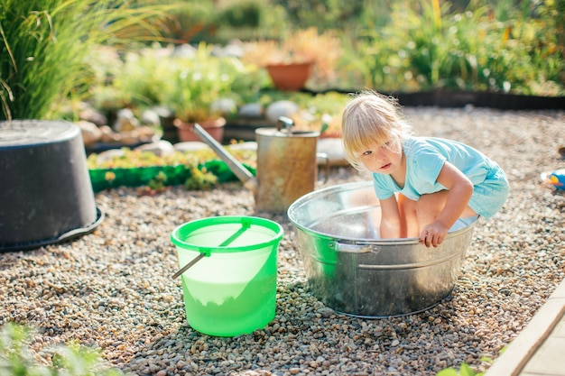 Kleines blondes mädchen, das am garten mit wasser in einem zinnbecken spielt.