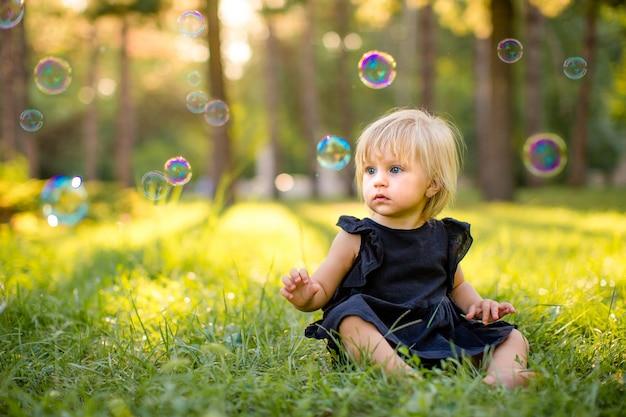 Kleines blondes mädchen, das auf einem gras in einem park sitzt und mit seife mit blasen spielt. sommerzeit, kindheit.