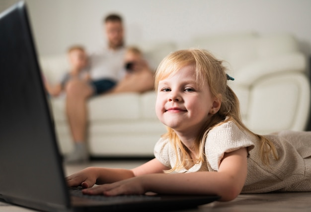 Kleines blondes mädchen, das auf einem laptop spielt