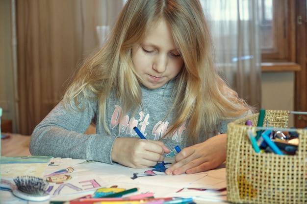 Kleines blondes mädchen, das auf ihrem buch zeichnet und spaß am spieltisch hat. kind mädchen macht ihre hausaufgaben zu hause.