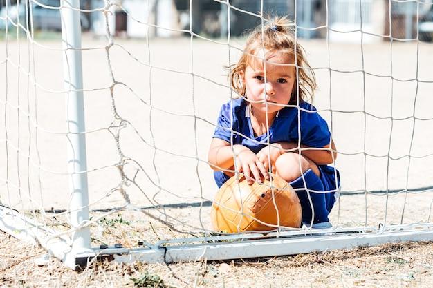 Kleines blondes mädchen, das blaue fußballuniform im tor mit einem ball trägt