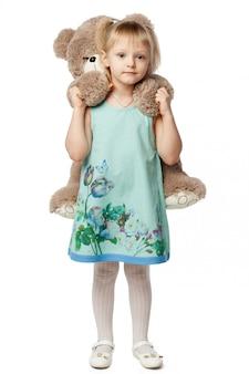 Kleines blondes mädchen, das ein teddybärspielzeug umarmt