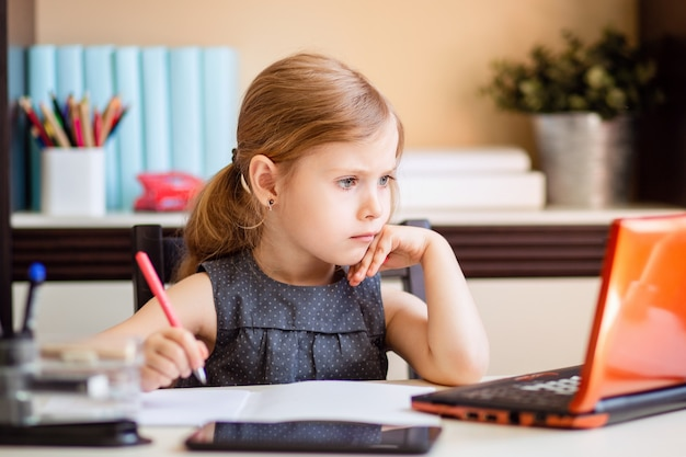 Kleines blondes mädchen, das hausaufgaben zu hause am tisch macht. das kind ist zu hause unterrichtet. ein mädchen mit hellem haar führt eine aufgabe online mit einem laptop und einem tablet-computer aus.