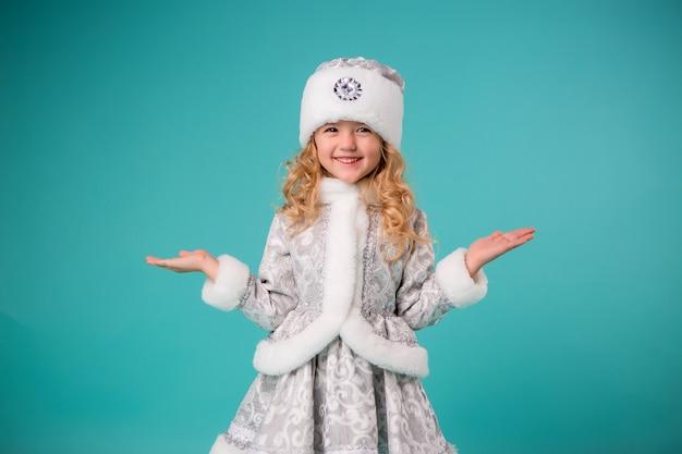 Kleines blondes mädchen, das im schneewittchen-kostümisolat auf blauer wand lächelt