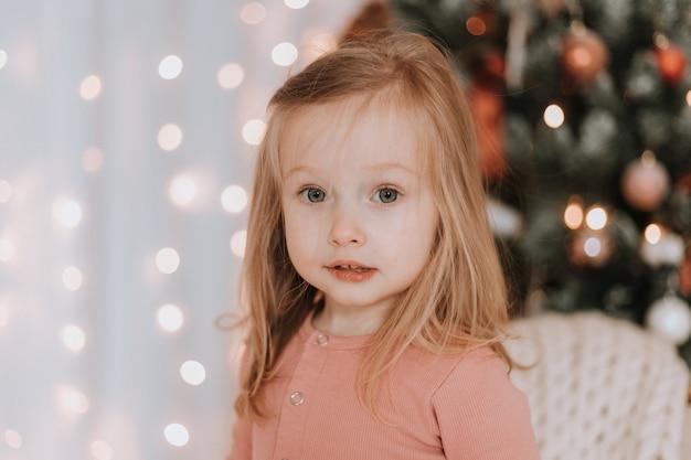 Kleines blondes mädchen, das in ein großes gestricktes plaid gehüllt ist, sitzt auf einem stuhl neben dem weihnachtsbaum