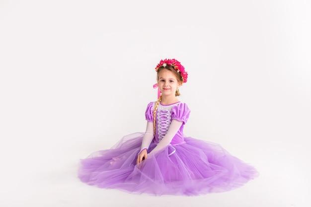 Kleines blondes mädchen, das purpurrotes feenhaftes prinzessinkleid auf weißem hintergrund trägt. kinderkostüm für silvesterparty
