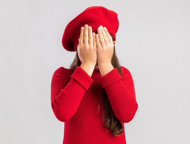 Kleines blondes mädchen, das rotes barett trägt, das gesicht mit den händen schließt, die auf weißer wand mit kopienraum lokalisiert werden?