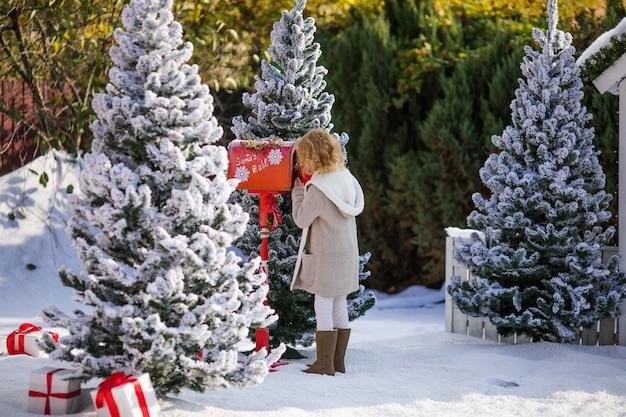 Kleines blondes mädchen, das sankt, weihnachtszeit ihren brief mit wunschliste sendet