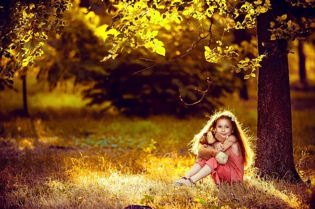 Kleines blondes mädchen, das unter einem birkenbaum mit einem spielzeug sitzt