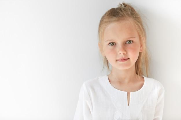 Kleines blondes mädchen, das weiße bluse trägt