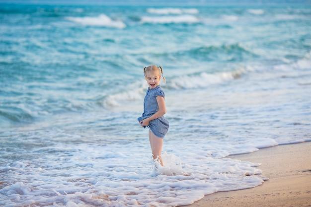 Kleines blondes mädchen im blauen kleid auf dem meer