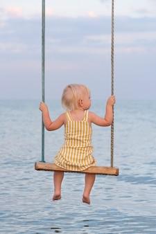 Kleines blondes mädchen im gelben kleid, das auf einer seilschaukel über meer sitzt. schaukel auf dem meer.