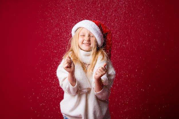 Kleines blondes mädchen im weihnachtsmannanzug
