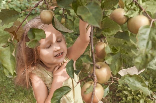 Kleines blondes mädchen in einem grünen kleid klammert sich mit geschlossenen augen an einen ast voller äpfel