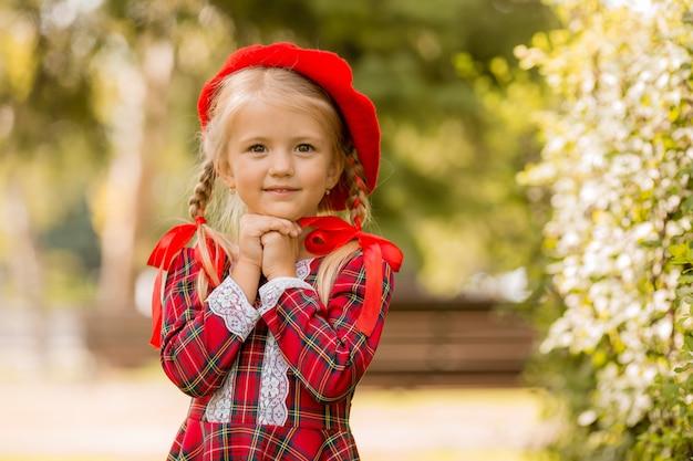Kleines blondes mädchen in einem roten kleid