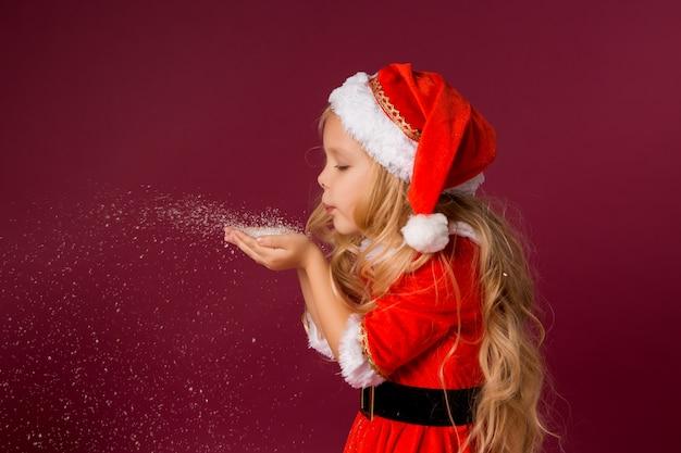 Kleines blondes mädchen in einem sankt-anzug weht schnee von ihren händen