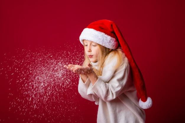 Kleines blondes mädchen in einem weihnachtsmannanzug bläst schnee von ihren händen