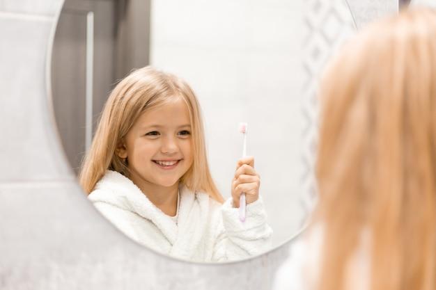 Kleines blondes mädchen in einem weißen bademantel putzt sich die zähne vor dem badezimmerspiegel