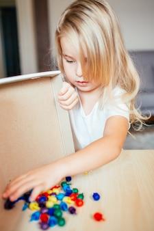 Kleines blondes mädchen in einem weißen t-shirt, das zu hause mit plastikmehrfarbenmosaik oder vorschule spielt. früherziehung konzept.