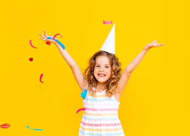 Kleines blondes mädchen in einer festlichen mütze und in einem weißen kleid fängt konfetti ein glückliches lächeln auf gelbem hintergrund.