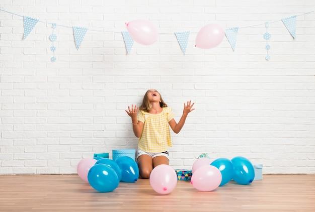 Kleines blondes mädchen in einer geburtstagsfeier, die mit ballonen spielt