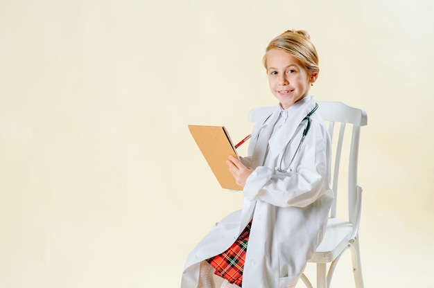 Kleines blondes mädchen in einer klage eines doktors macht einen eintrag in einem notizbuch