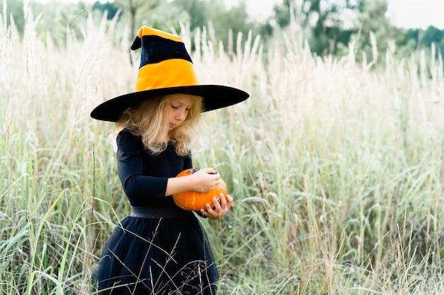 Kleines blondes mädchen in schwarzem anzug und hexenhut, halloween mit einem kürbis in den händen.