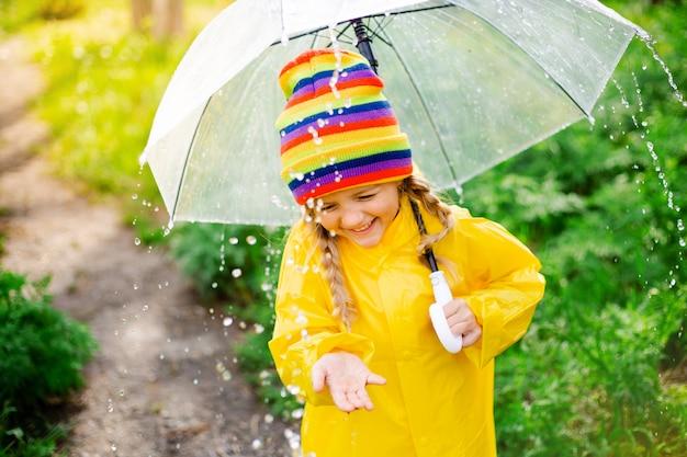 Kleines blondes mädchen lächelt springt auf pfützen im frühling in gelbem regenmantel und gummistiefeln mit regenschirm