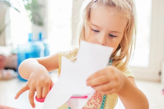 Kleines blondes mädchen mit der schere an der vorschule. education.portrait eines kleinen netten babys, das ein papier schneidet.