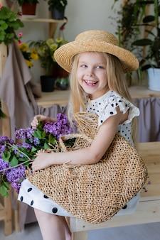 Kleines blondes mädchen mit einem strauß lila blumen sitzt auf einem holzstuhl im zimmerlebensstil