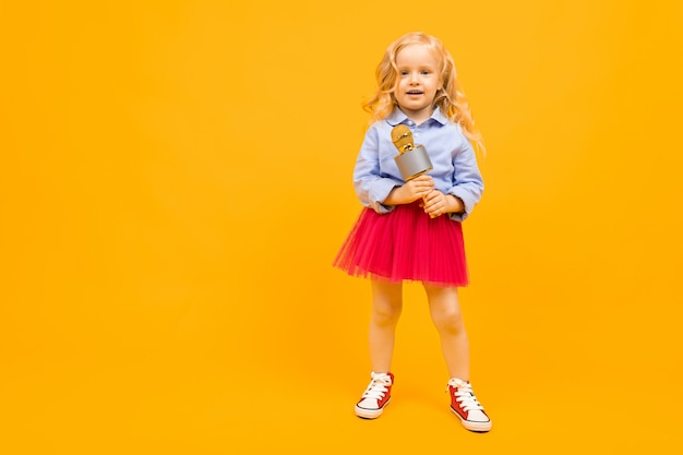 Kleines blondes mädchen mit mikrofon auf einem orange hintergrund mit kopienraum