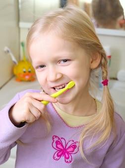 Kleines blondes mädchen mit zahnbürste