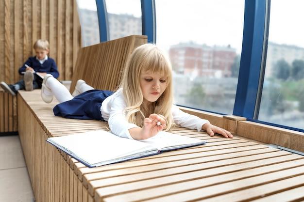 Kleines blondes mädchen schreibt einem jungen eine romantische notiz.