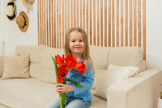Kleines blondes mädchen sitzt auf einem beigen sofa mit einem strauß roter tulpen im raum