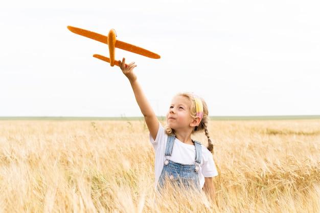 Kleines blondes mädchen spielt flugzeug im bereich roggen, getreideernte.