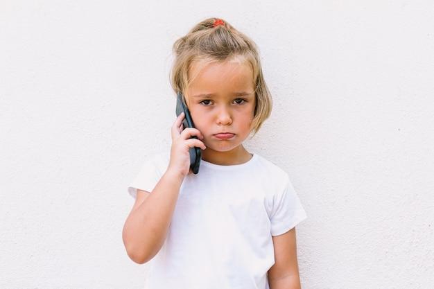 Kleines blondes mädchen trägt weißes t-shirt, telefoniert mit dem handy und sieht wütend aus