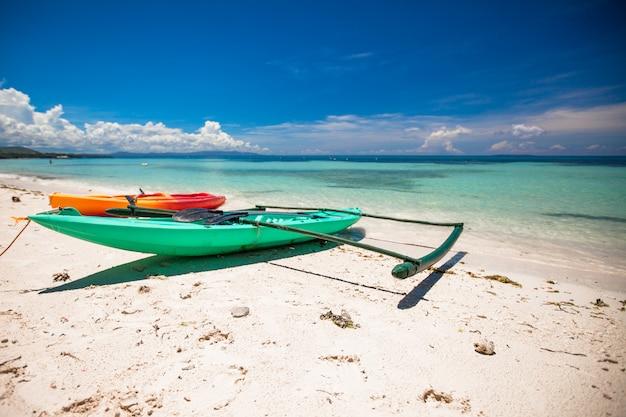 Kleines boot auf dem weißen sandigen tropischen strand